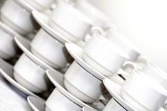 Filas de las tazas de café con los platillos Fotos de archivo libres de regalías