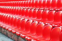 Filas de los asientos vacíos rojos del estadio imagen de archivo