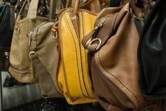 Filas de los bolsos de cuero en tienda. Imagen de archivo libre de regalías