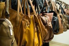 Filas de los bolsos de cuero en tienda. Fotos de archivo