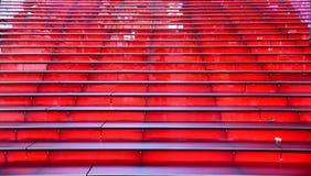 Filas de los pasos illuminating rojos que miran para arriba sin gente Imágenes de archivo libres de regalías