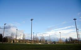 Filas de los polos de iluminación en los campos de fútbol Imagen de archivo libre de regalías