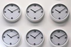 Filas de los relojes plásticos blancos de la pared en el fondo blanco Imagen de archivo