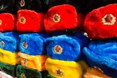 Filas de los sombreros rusos del invierno de diversos colores con los emblemas del ejército en el mercado callejero en la calle v Fotos de archivo libres de regalías