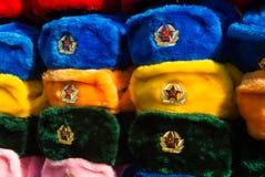 Filas de los sombreros rusos del invierno de diversos colores con los emblemas del ejército en el mercado callejero en la calle v Imágenes de archivo libres de regalías