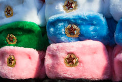 Filas de los sombreros rusos del invierno de diversos colores con los emblemas del ejército en el mercado callejero en la calle v Foto de archivo libre de regalías