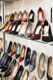 Filas de los zapatos de las mujeres hermosas en estantes de una tienda Fotos de archivo libres de regalías