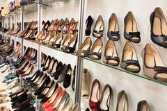 Filas de los zapatos de las mujeres hermosas en estantes de una tienda Imagen de archivo