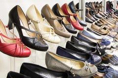 Filas de los zapatos de las mujeres hermosas en estantes de una tienda Fotografía de archivo libre de regalías
