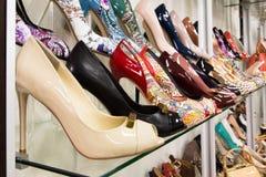 Filas de los zapatos de las mujeres hermosas en estantes de una tienda Fotografía de archivo