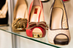 Filas de los zapatos de las mujeres hermosas en estantes de una tienda Imagen de archivo libre de regalías