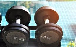 Filas de pesas de gimnasia en el gimnasio Fotos de archivo