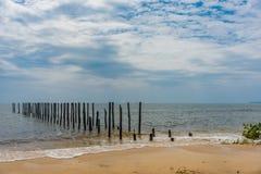 2 filas de posts de madera salen adentro a un mar tranquilo del paraíso apagado de a Fotografía de archivo