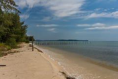 2 filas de posts de madera salen adentro a un mar tranquilo del paraíso apagado de a Fotos de archivo