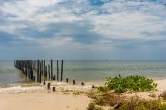 2 filas de posts de madera salen adentro a un mar tranquilo del paraíso apagado de a Imágenes de archivo libres de regalías