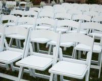 Filas de sillas blancas vacías en un césped verde Fotografía de archivo libre de regalías