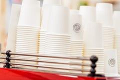 Filas de tazas blancas al revés de la cartulina para las bebidas, vajilla disponible para el caffee, camiseta, inexistente abstra Imágenes de archivo libres de regalías