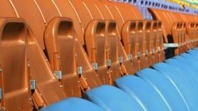 Filas del asiento en estadio con las sillas dobladas Ciérrese encima de asientos anaranjados y azules vacíos almacen de video