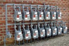 Filas del contador de gas en la nueva pared comercial del edificio Fotos de archivo