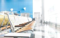 Asientos en pasajeros que esperan del pasillo del aeropuerto para. Imagen de archivo libre de regalías