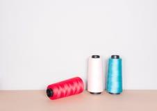 Filati cucirini multicolori su chiaro fondo Fotografie Stock