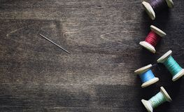 Filato cucirino su un fondo di legno Insieme dei fili sulle bobine Immagini Stock Libere da Diritti