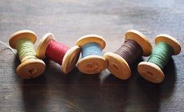 Filato cucirino su un fondo di legno Insieme dei fili sulle bobine Fotografie Stock