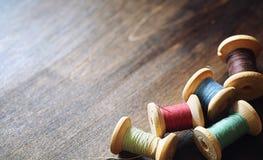 Filato cucirino su un fondo di legno Insieme dei fili sulle bobine Immagine Stock