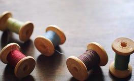 Filato cucirino su un fondo di legno Insieme dei fili sulle bobine Immagine Stock Libera da Diritti