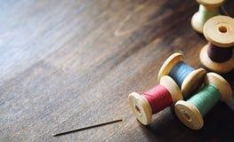 Filato cucirino su un fondo di legno Insieme dei fili sulle bobine Fotografia Stock