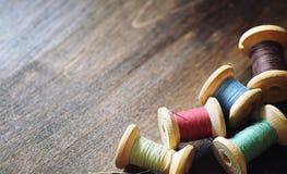 Filato cucirino su un fondo di legno Insieme dei fili sulle bobine Fotografia Stock Libera da Diritti