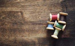 Filato cucirino su un fondo di legno Insieme dei fili sulle bobine Fotografie Stock Libere da Diritti