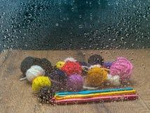 Filato rimanente su una tavola di legno con gli uncinetti, visti attraverso una finestra con le gocce di pioggia immagine stock