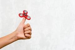 Filatore di irrequietezza Filatore rosso della mano, giocattolo irritantesi della mano che gira sulla mano del ` s del bambino Di Immagini Stock Libere da Diritti