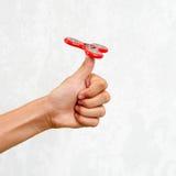 Filatore di irrequietezza Filatore rosso della mano, giocattolo irritantesi della mano che gira sulla mano del ` s del bambino Di Fotografia Stock