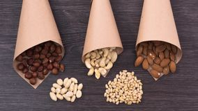 Filbert, cashew and almonds fall in paper bags near a handful of pine nuts and peanuts. Stop motion stock footage