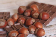 Filbert and chocolate on wooden background Royalty Free Stock Photography