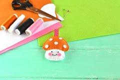 Filc zabawki pieczarka, nić, igła, nożyce, zielony drewniany tło, opróżnia przestrzeń dla teksta Zdjęcie Stock