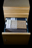 File Cabinet and 43 Folders. Wooden rolling file cabinet with a drawer opened, showing 43 hanging folders royalty free stock photography
