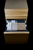 File Cabinet and 43 Folders. Wooden rolling file cabine t with a drawer opened, showing 43 hanging folders royalty free stock images