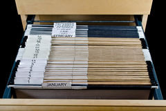 File Cabinet and 43 Folders. Wooden rolling file cabinet with a drawer opened, showing 43 hanging folders stock image