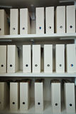 File Cabinet in Office. Front view of shelves with identical white documentation folders in office Stock Image