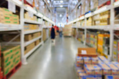 File degli scaffali con le scatole nell'interno moderno del magazzino Immagine Stock