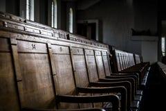 File dei banchi di chiesa di legno giù in una costruzione chiusa Immagini Stock
