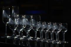 File dei bicchieri di vino vuoti e dei vetri vuoti per vodka Immagine Stock
