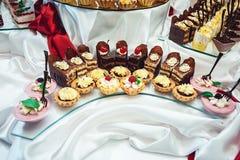 File dei dolci differenti su un supporto di vetro Fotografia Stock