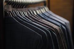 File dei rivestimenti del vestito del ` s degli uomini nel suitshop Immagine Stock