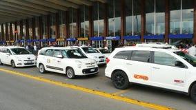 File dei taxi bianchi che aspettano i clienti alla stazione ferroviaria di estremità stock footage
