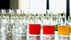 File dei vetri con le bevande alcoliche sulla tavola fotografie stock