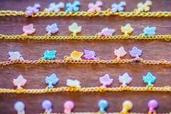 File della catena dorata del braccialetto con i pendenti svegli da vendere nel negozio di gioielli Le catene fatte a mano dorate  Immagini Stock